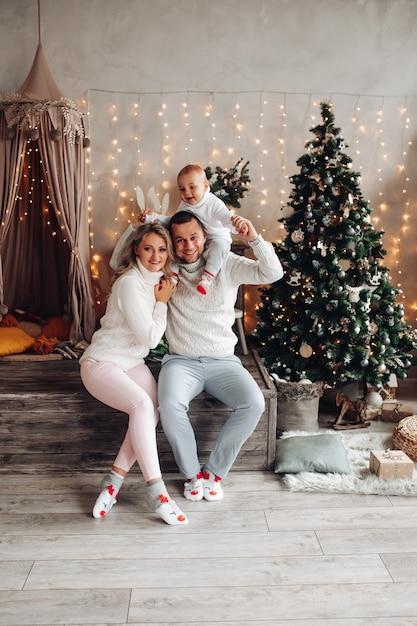 装飾された部屋で彼の美しい妻の横に座っている間彼の肩に子供を抱いて若い男 無料写真