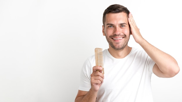 Young man holding comb and set his hair against white background Free Photo