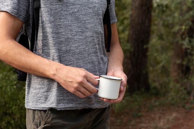 Молодой человек держит чашку Premium Фотографии