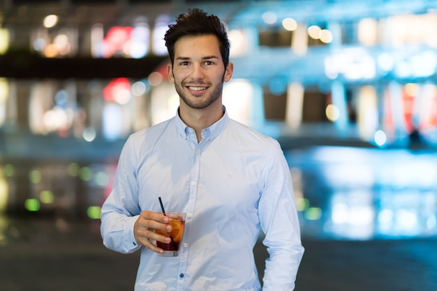 Young man holding a drink at a night club outdoor Premium Photo