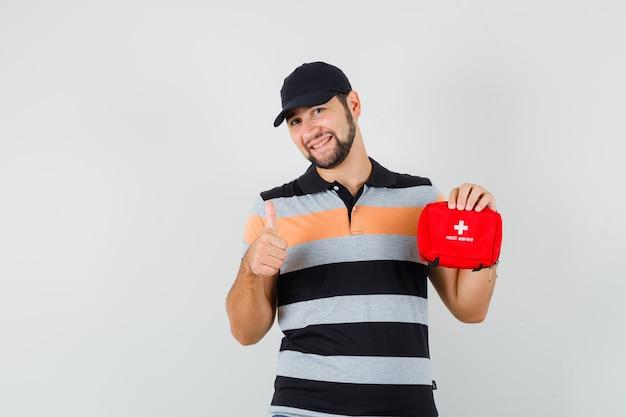 Молодой человек держит аптечку, показывает палец вверх в футболке, кепке и рад. передний план. Бесплатные Фотографии