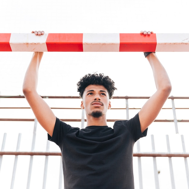 Young man holding on football goal and looking away Free Photo