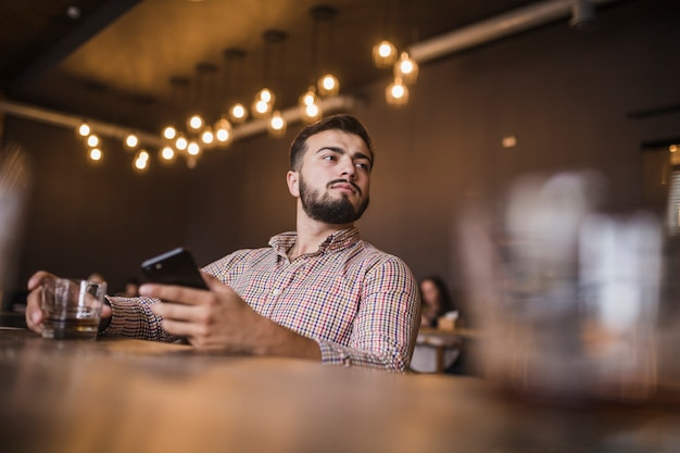 Молодой человек, проведение стакан питьевой и мобильный телефон, глядя в сторону Бесплатные Фотографии