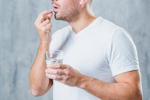 A young man holding glass of water taking medicine Free Photo