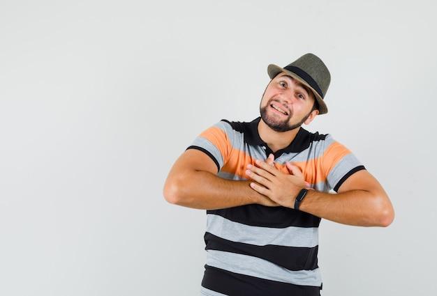 Tシャツ、帽子、感謝の気持ちを込めて、正面から胸に手をつないでいる若い男。 無料写真