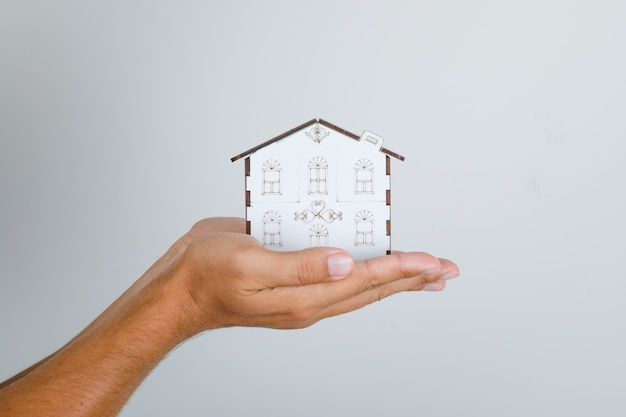 Young man holding house model in his hands. Free Photo