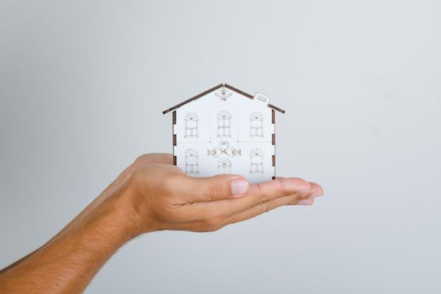 Молодой человек держит в руках модель дома. Бесплатные Фотографии