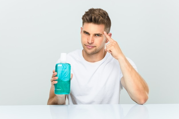 Young man holding a mouthwash pointing his temple with finger, thinking, focused on a task. Premium Photo
