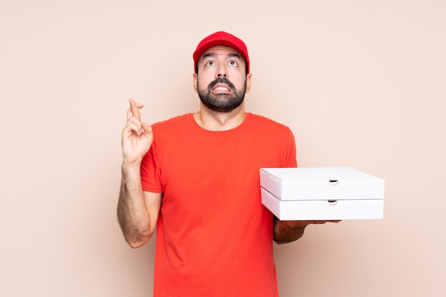 Young man holding a pizza with fingers crossing and wishing the best Premium Photo