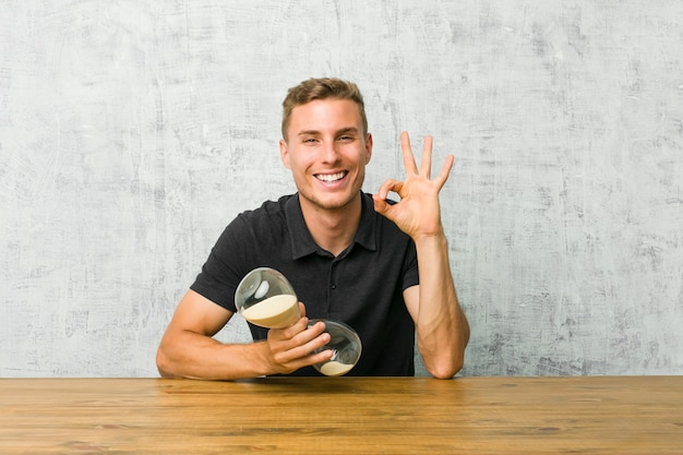 Young man holding a sand timer on a table winks an eye and holds an okay gesture with hand. Premium Photo