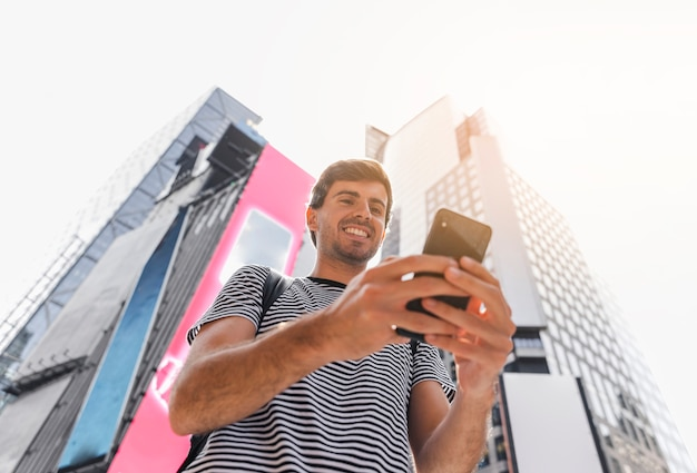 Young man holding a smartphone with both hands Free Photo