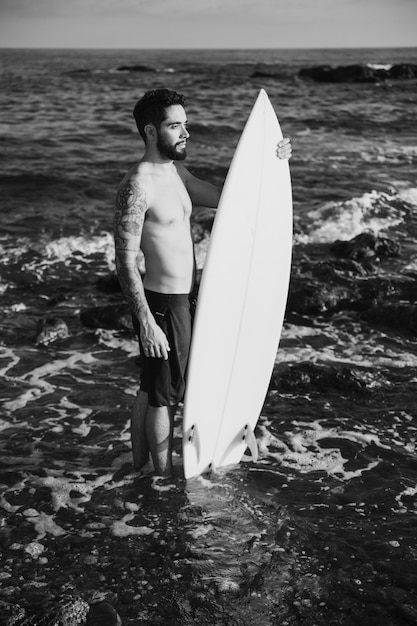 Young man holding surf board in water Free Photo