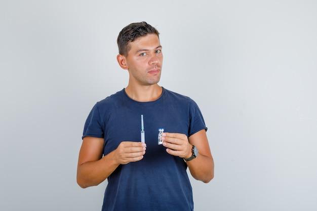 Giovane che tiene la siringa e la fiala in maglietta blu scuro e che osserva attento. vista frontale. Foto Gratuite