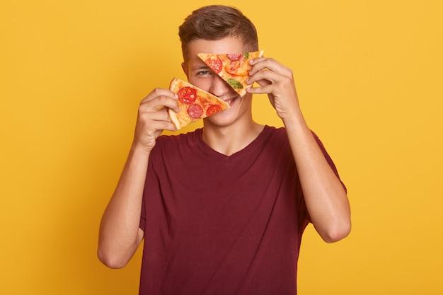 若い男が2つのおいしいピザを手に持って、おいしい製品で彼の目を覆っています。 無料写真