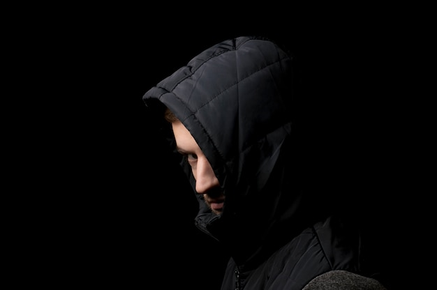 Premium Photo   Young man in a hood on a black