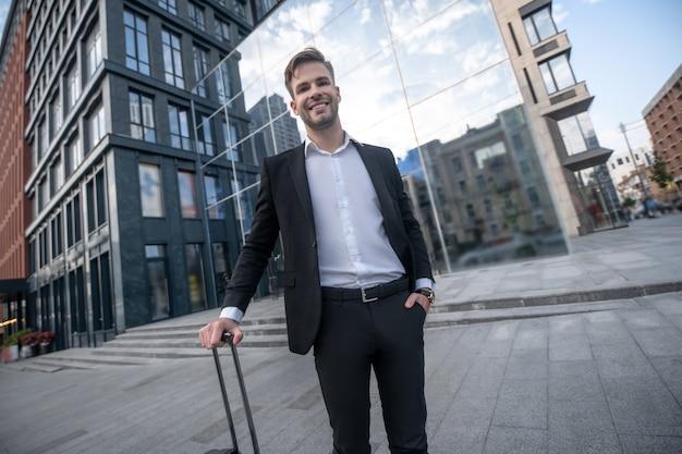 Молодой человек в черном костюме и чемодане стоит на улице Premium Фотографии