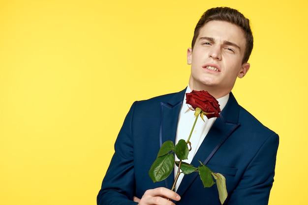 彼の手にバラとセクシーな表情のクラシックなスーツの若い男 Premium写真