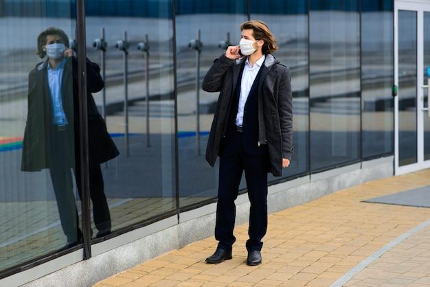 外の医療マスクの若い男、お金、危機、貧困、苦難。コロナウイルス隔離。 Premium写真