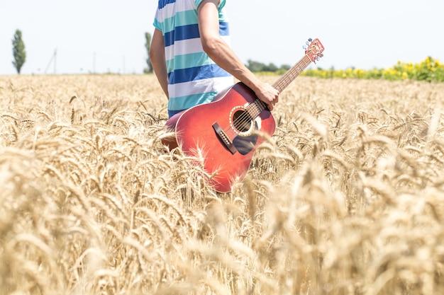 ギターと麦畑の若い男 無料写真