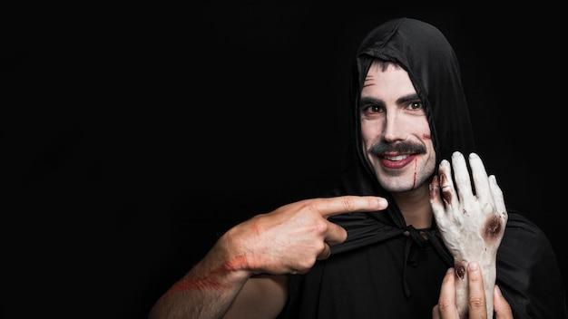 Молодой человек в черном плаще, показывая искусственную руку трупа Бесплатные Фотографии