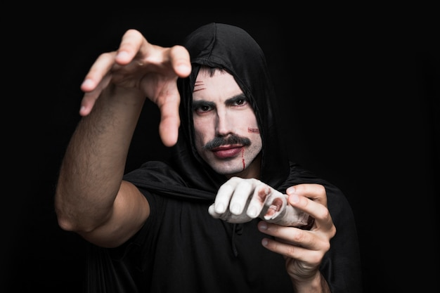 young man in black clothes posing in studio with corpse hand photo
