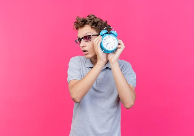 ピンクの壁の上に立って心配して脇を見て目覚まし時計を保持している灰色のポロシャツを着た黒い眼鏡の若い男 無料写真