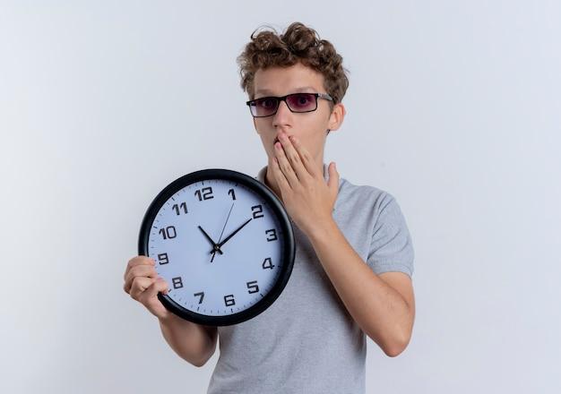 白い壁の上に立ってショックを受けている手で口を覆っている壁時計を保持している灰色のポロシャツを着ている黒い眼鏡の若い男 無料写真