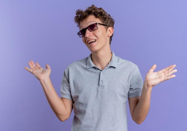 회색 폴로 셔츠를 입고 검은 안경에 젊은 남자가 파란색 벽 위에 서있는 대답이없는 혼란스럽고 불확실한 제기 손을보고 무료 사진