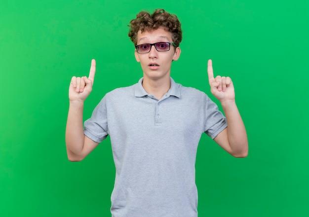 녹색 벽 위에 서서 놀란 Idex 손가락으로 가리키는 회색 폴로 셔츠를 입고 검은 안경에 젊은 남자 무료 사진
