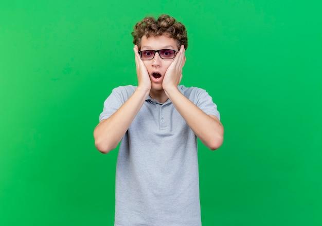 녹색 위에 충격을 받고 얼굴에 손으로 회색 폴로 셔츠를 입고 검은 안경에 젊은 남자 무료 사진