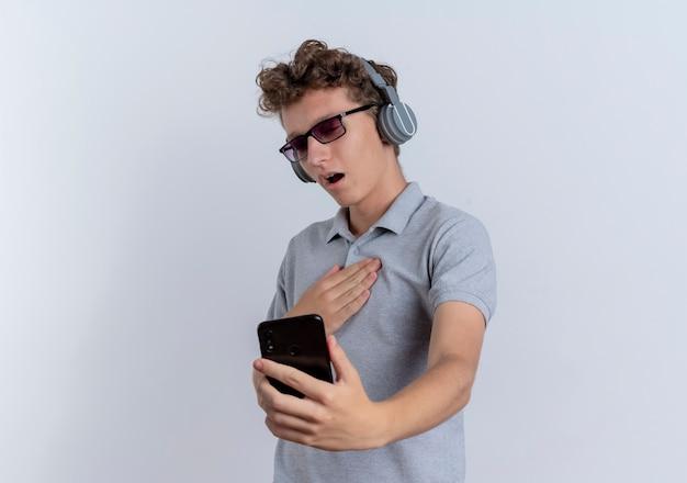 白い壁の上に立って感謝を感じて彼のスマートフォンの画面を見ているヘッドフォンで灰色のポロシャツを着ている黒い眼鏡の若い男 無料写真