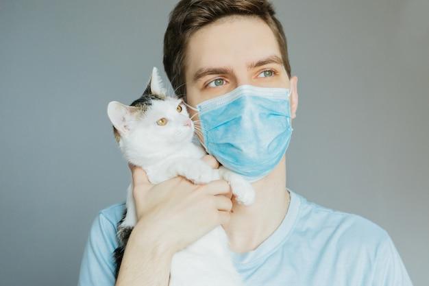 Молодой человек в синей рубашке и медицинской маске с полосатый кот на руках на сером фоне Premium Фотографии