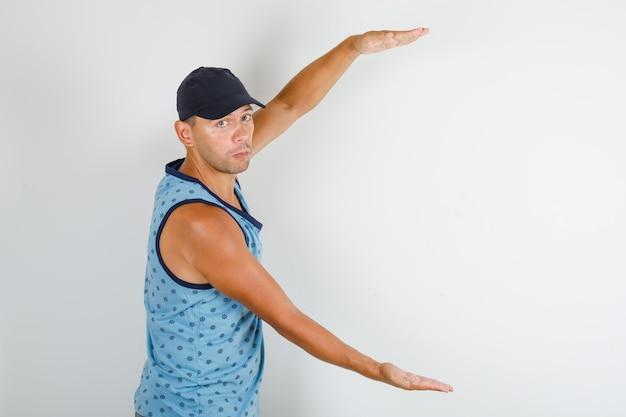 Молодой человек в синей майке с крышкой, показывающей знак большого размера. Бесплатные Фотографии