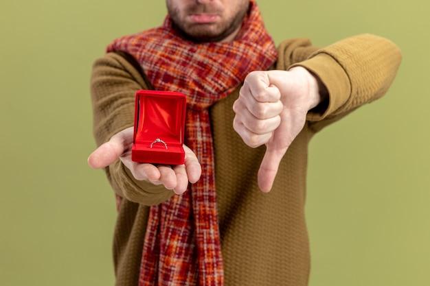 Молодой человек в повседневной одежде с шарфом на шее показывает красную коробку с обручальным кольцом, показывая большие пальцы руки вниз концепцию дня святого валентина, стоящую на зеленом фоне Бесплатные Фотографии