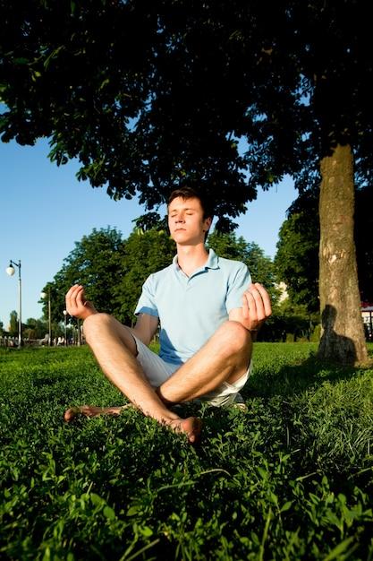 푸른 잔디에 앉아 여름 맑은 날에 공원에서 햇빛에 명상 캐주얼 의류에 젊은 남자. 내면의 자유와 행복한 라이프 스타일 컨셉 프리미엄 사진