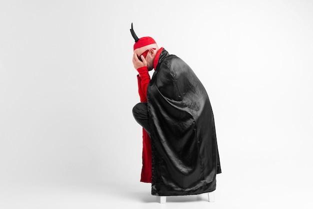 仮面舞踏会の服と赤い帽子をかぶった絶望の若い男は、白い背景の手で顔を覆っている黒い角があります。 Premium写真
