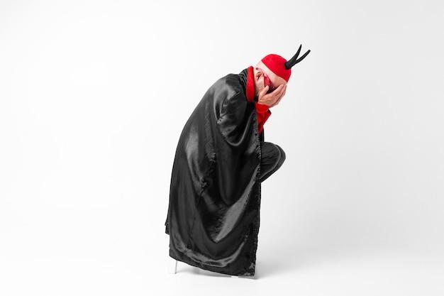 仮面舞踏会の服と手で顔を覆っている黒い角の赤い帽子で絶望している若い男 Premium写真