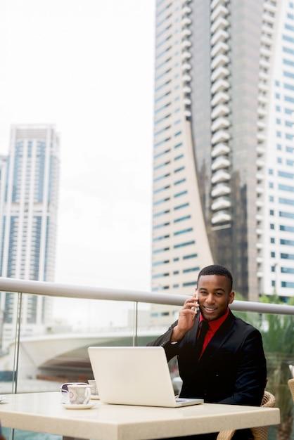 フォーンコールをしながらランチを持っているフォーマルな服装の若い男 Premium写真
