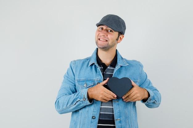 ジャケットを着た若い男、ハート型の箱を持って喜んでいるキャップ 無料写真
