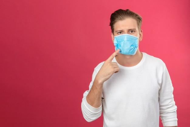 孤立したピンクの背景に病気の概念を得ることを避けるためにマスクを着用する必要がある医療マスクで彼の指を指しているカメラを見て医療用防護マスクの若い男 無料写真