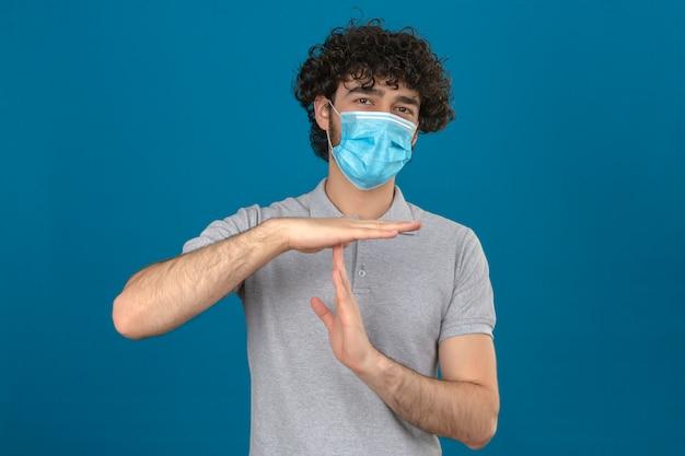 Молодой человек в медицинской защитной маске выглядит больным и усталым, делая жест тайм-аута руками на синем фоне Бесплатные Фотографии