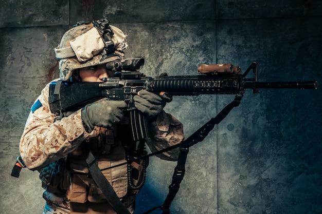 軍服の若い男がスタジオで暗い背景に現代のmerc兵 Premium写真