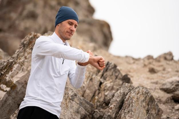 Молодой человек на природе смотрит на часы возле скал Бесплатные Фотографии