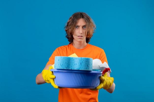 Молодой человек в оранжевой футболке в резиновых перчатках держит таз с чистящими средствами, глядя в камеру, недовольный гневным выражением лица, стоящего на синем фоне Бесплатные Фотографии