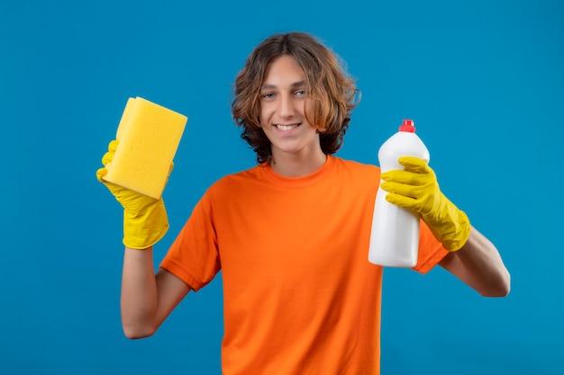 クリーニング用品のボトルを保持しているゴム手袋を身に着けているオレンジ色のtシャツの若い男と青い背景の上に元気に立って笑顔のカメラを見てスポンジ 無料写真