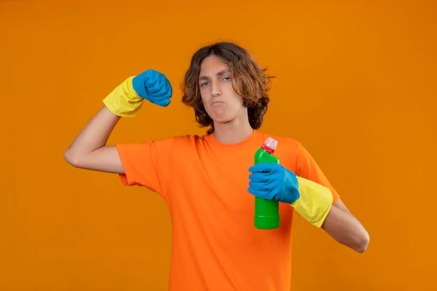 Молодой человек в оранжевой футболке в резиновых перчатках держит бутылку чистящих средств, сжимая кулак, радуется своему успеху и победе, выглядит уверенно, самодовольно и гордо стоит Бесплатные Фотографии