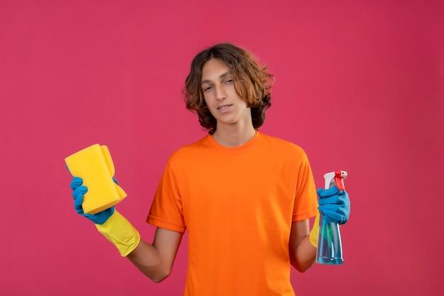 ピンクの背景の上に立って自信を持って笑顔でカメラを見てクリーニングスプレーとスポンジを保持しているゴム手袋をはめてオレンジ色のtシャツの若い男 無料写真