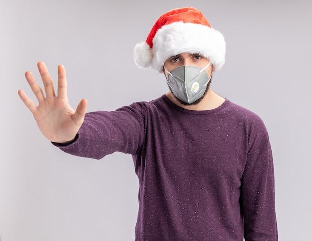 Молодой человек в фиолетовом свитере и шляпе санта-клауса в лицевой защитной маске смотрит в камеру с серьезным лицом, делая жест остановки с рукой, стоящей на белом фоне Бесплатные Фотографии