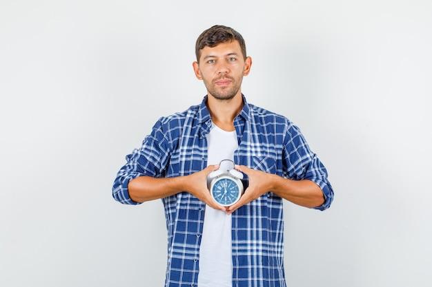 Молодой человек в рубашке держит будильник и смотрит пунктуально, вид спереди. Бесплатные Фотографии