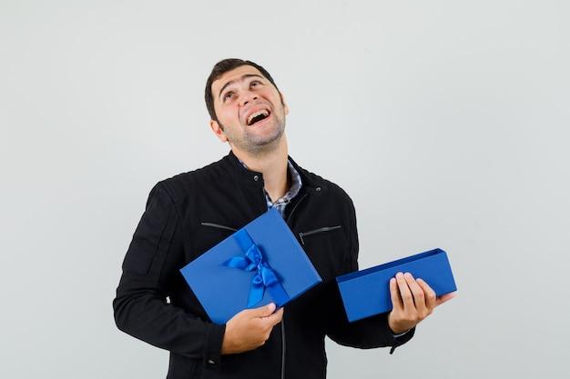 シャツを着た若い男、開いたプレゼントボックスを保持し、感謝しているジャケット 無料写真